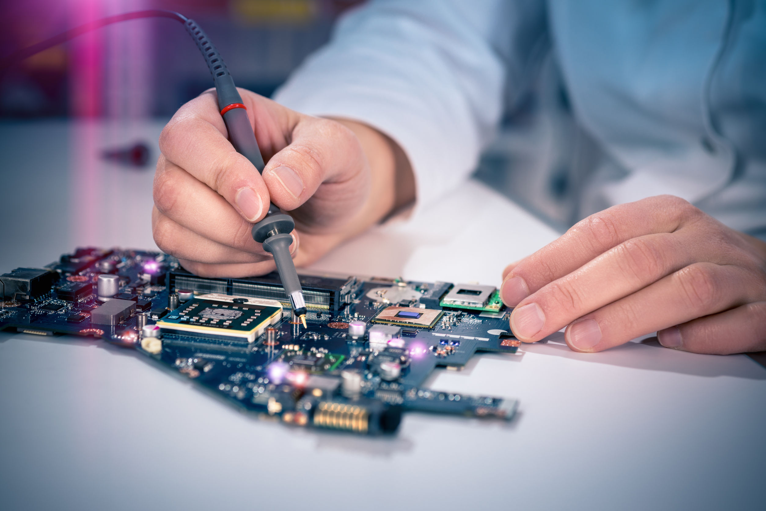 tech fixes motherboard in service center. shallow dof, focus on hands, image is toned with extra light effects