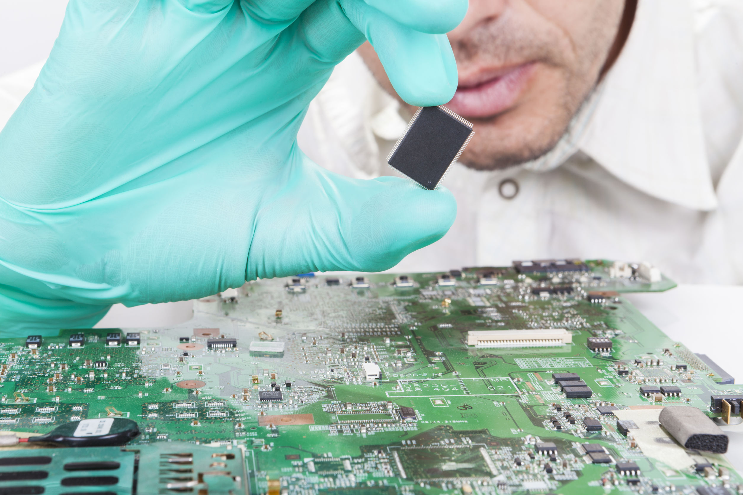 Holding Microchip on electronic circuit board with Gloves